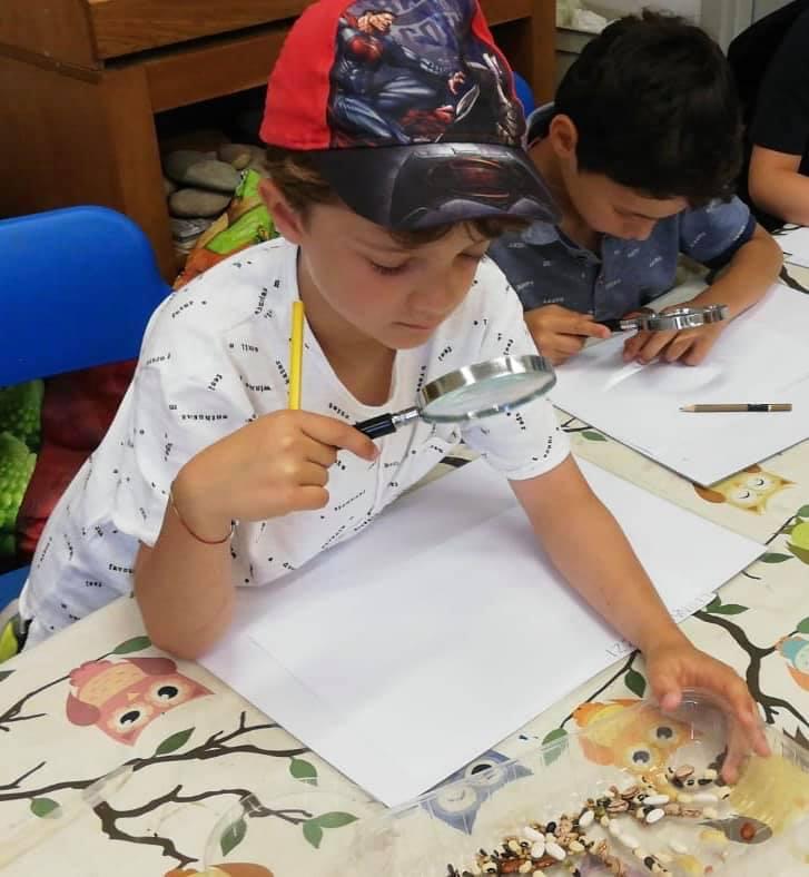 foto di bambini con lente di ingrandimento che sperimentano