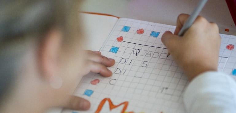 foto bambina che scrive sul quaderno