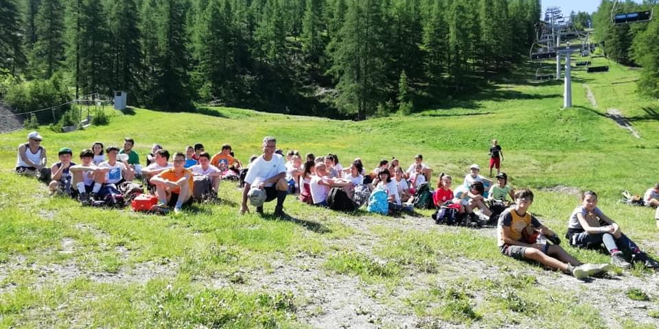 foto bambini seduti in ricreazione sul prato